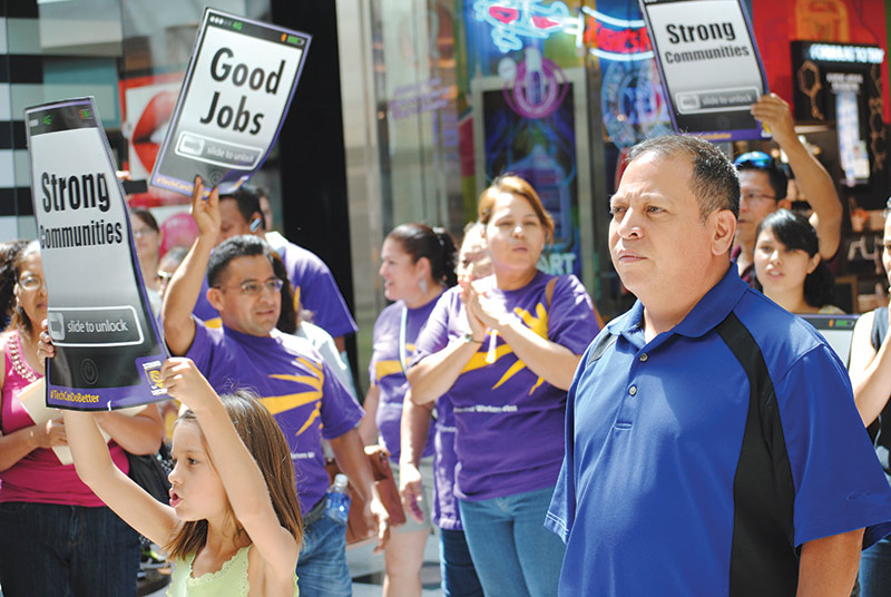 United Service Workers West President Lino Pedres (right) led marchers inside the Apple store.