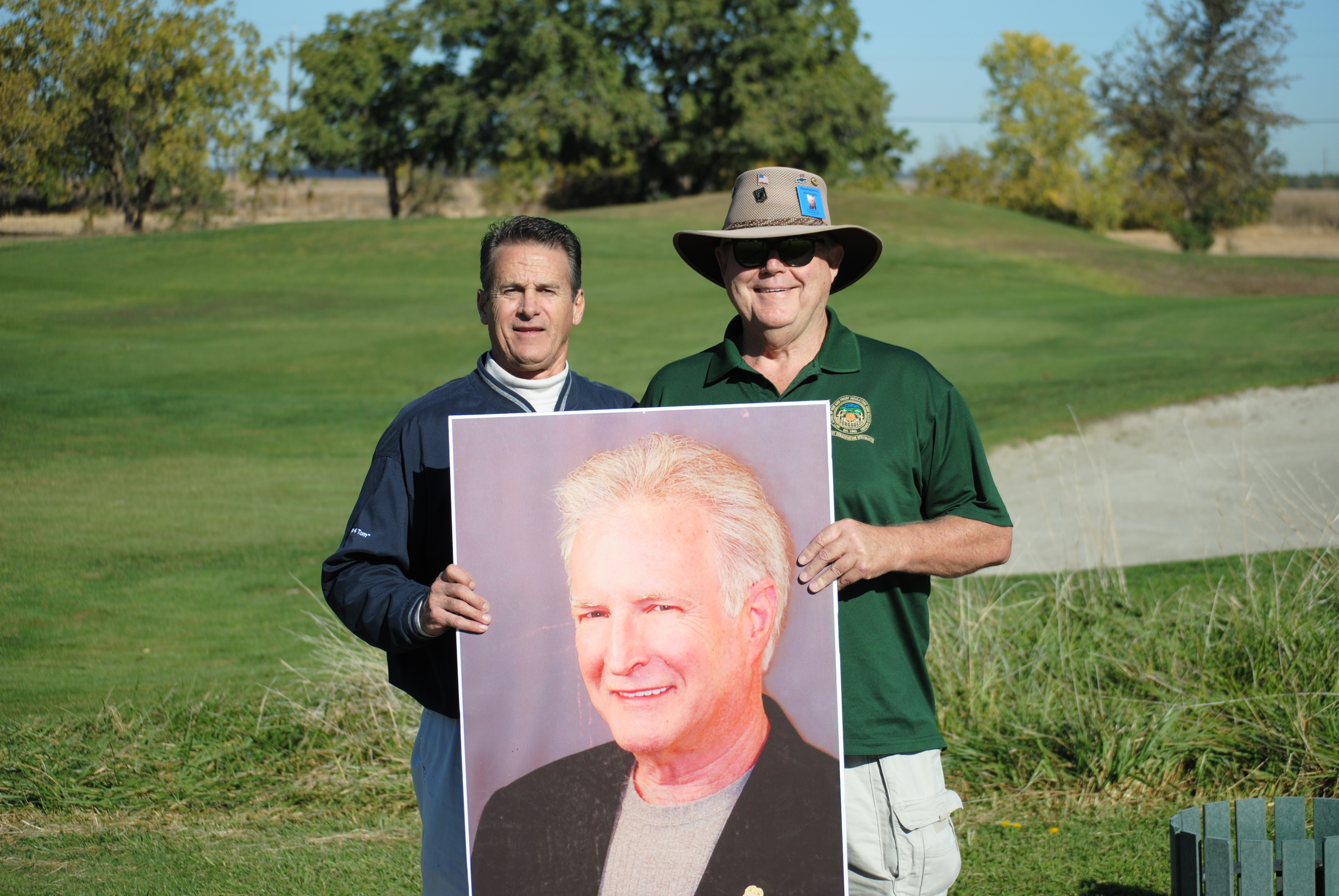 Greg Larkins and Geoff Millar of Asbestos Workers Local 16 pose with a photo of Tom Lawson during this year's annual golf tournament.